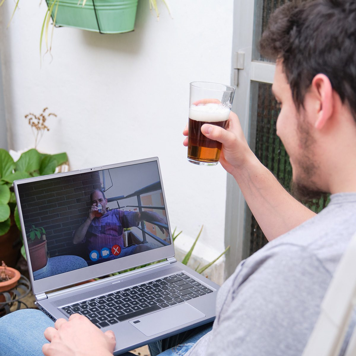 Man Talking And Having A Beer With His Father On A Videocall