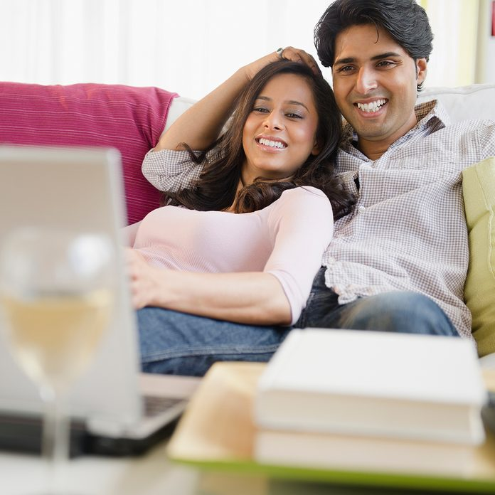 Mixed Race Couple Watching Television On Laptop