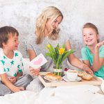 Mother´s Day   Two Children Surprise Their Mother With Breakfast In Modern Bed