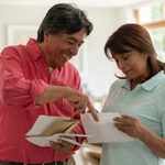 Cheerful Senior Couple At Home Looking At Their Mail While Talking And Smiling