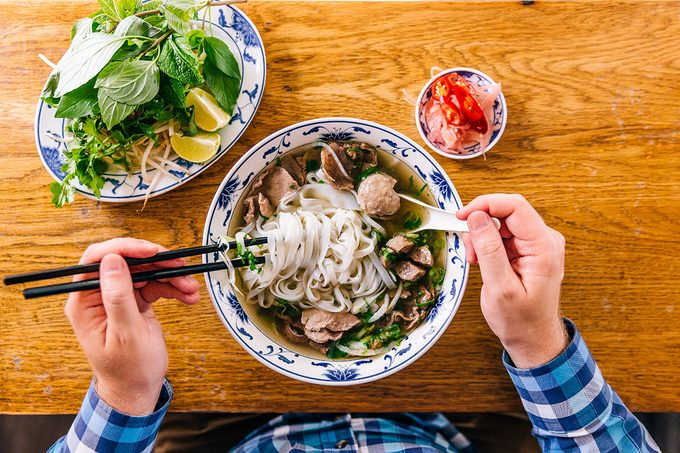 Man Eating Vietnamese Pho Soup With Noodles And Beef, Personal Perspective View