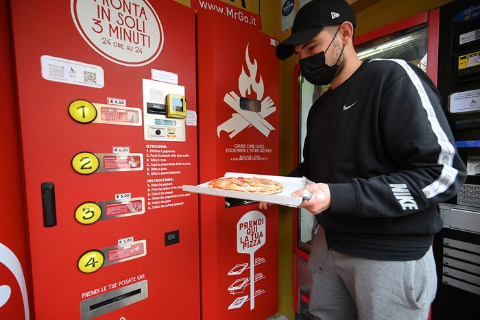 ROME, May 4, 2021 -- A man collects his order from an automatic pizza vending machine in downtown Rome, Italy, on May 4, 2021. The vending machine is capable of kneading, seasoning, cooking and delivering the pizza in a carton box in three minutes only. (Photo by Alberto Lingria/Xinhua via Getty) (Xinhua/Alberto Lingria via Getty Images)