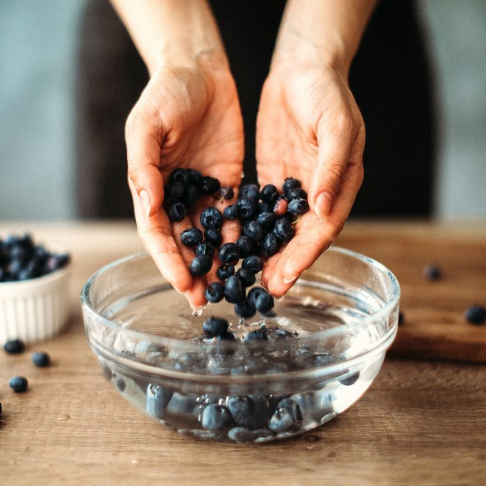 how to wash berries Unrecognizable woman cleaning blueberries in bowl with water on kitchen counter