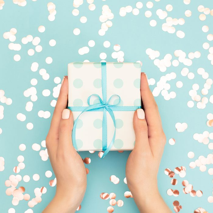 classic wedding gifts Womans hands holding gift or present box decorated confetti on pink pastel table top view. Flat lay composition for birthday or wedding