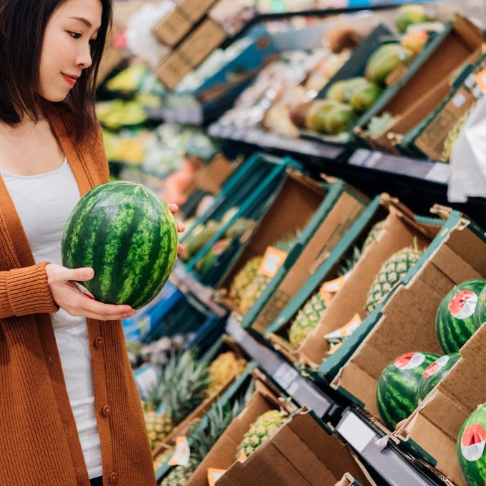 Young Asian Woman Shopping Fruits In Grocery Store