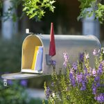 open mailbox with mail and flowers