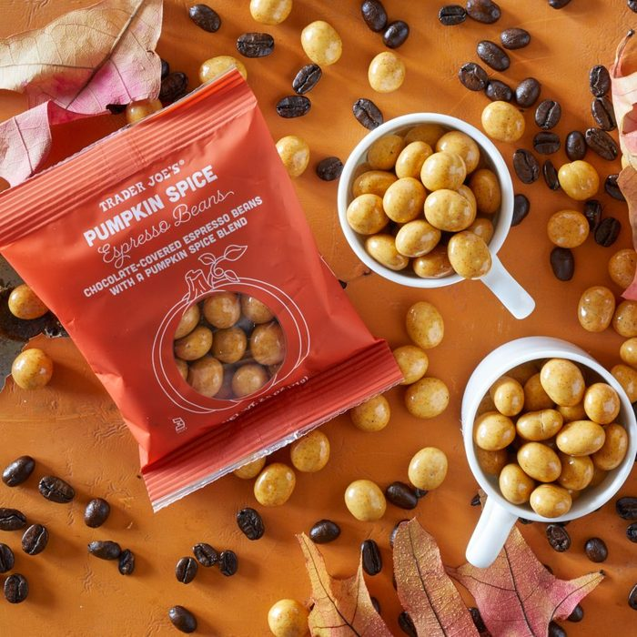 Trader Joe's Pumpkin Espresso Beans piled in two espresso cups, and scattered on surface with coffee beans and fall leaves