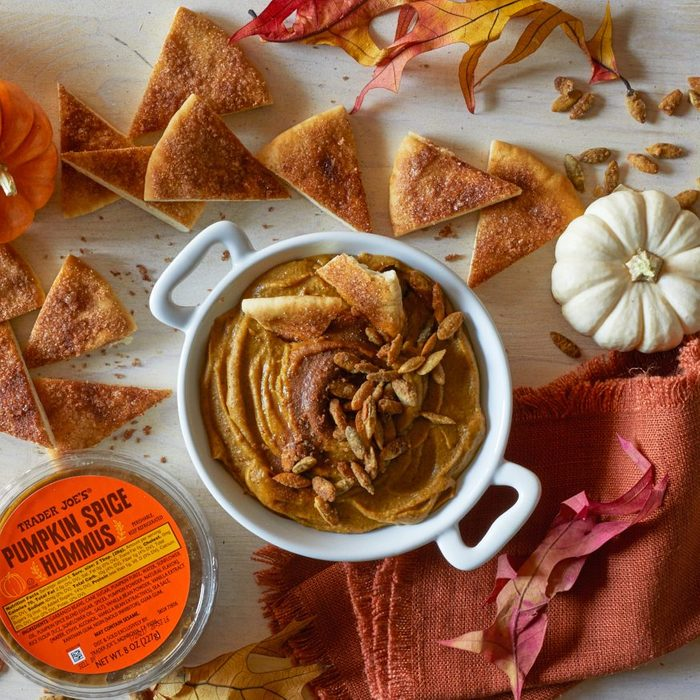 Trader Joe's Pumpkin Spice Hummus in a crock, sprinkled with pumpkin spiced pumpkin seeds and cinnamon and sugar. Pita bread wedges coated with cinnamon sugar and fall decorations surrounding