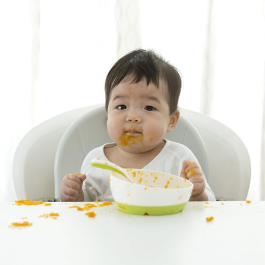 Asian baby learning self feeding.