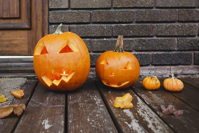 two carved pumpkins and two mini pumpkins outside on a porch for halloween