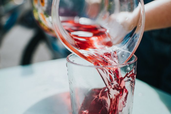 pouring red fruit juice into glass