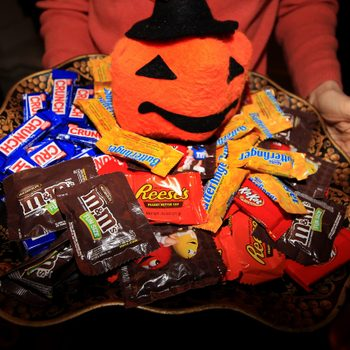 anonymous person holds out a dish of halloween candy